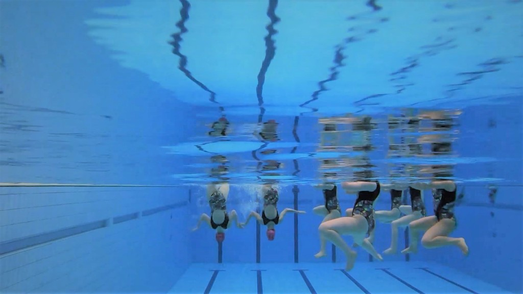 An underwater view of Edinburgh Synchro swimmers performing a combo routine - some swimmers doing a figure, others doing arm movements