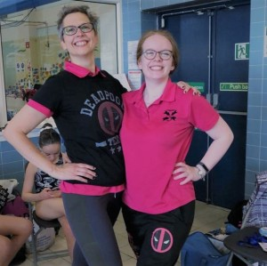 Vicky and Sarah standing side by side, smiling. Vicky wearing a black tshirt with deadpool logo, Sarah wearing and Edinburgh Synchro top with deadpool logo bottoms